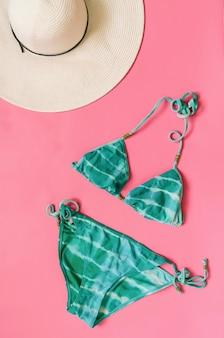 Maillot de bain bikini aigue-marine et chapeau de paille disposés sur fond rose clair.