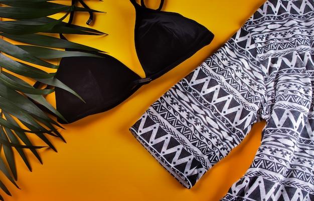 Maillot de bain bikini en velours noir, cape de plage et feuilles de palmier tropical