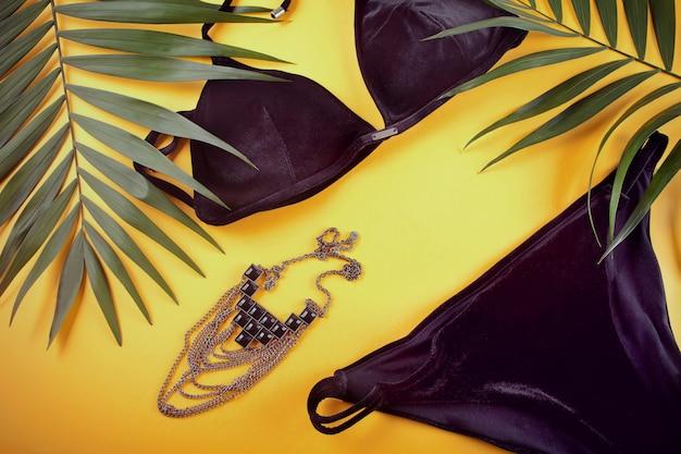 Maillot de bain bikini en velours noir, collier et feuilles de palmier tropical