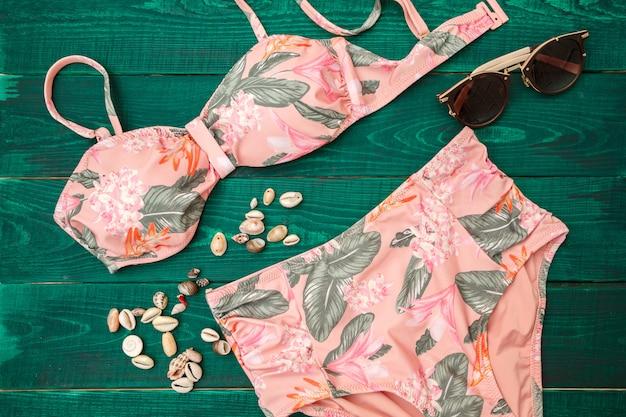Maillot de bain coloré avec des lunettes de soleil et des coquillages. la vue d'en haut