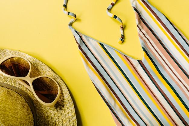Maillot de bain rayé, lunettes de soleil, chapeau de paille sur fond jaune, pose à plat. accessoires de plage pour femmes. fond d'été. concept de voyage. vue de dessus. photo de haute qualité