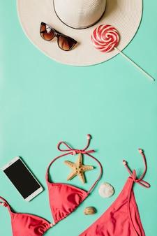 Maillots de bain femme et accessoires de vacances sur fond pastel plat avec espace copie