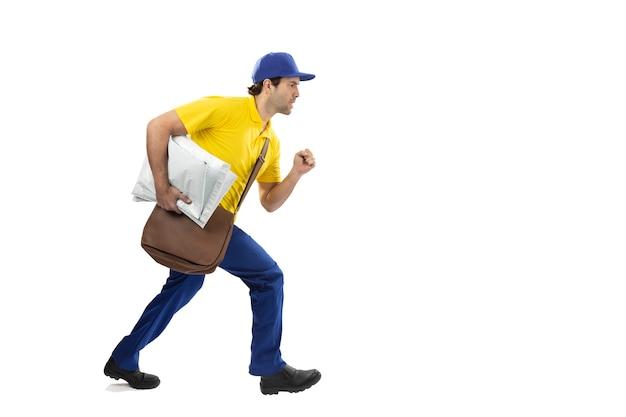 Mailman brésilien en cours d'exécution avec un paquet sur un fond blanc. copie espace.
