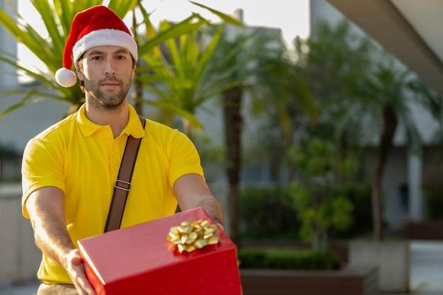 Mailman brésilien habillé en père noël offrant un cadeau. achat en ligne en cours de livraison.