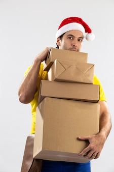 Mailman brésilien habillé en père noël offrant un cadeau sur un fond blanc. copie espace.