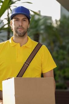 Mailman brésilien livrant un colis dans la rue. achat internet livré à domicile.