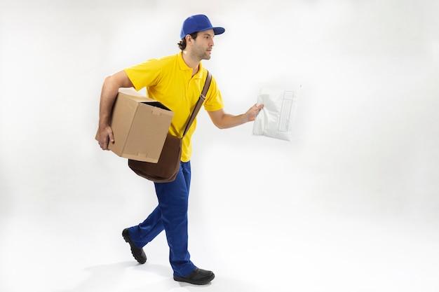 Mailman en cours d'exécution avec un paquet sur un mur blanc. copie espace.