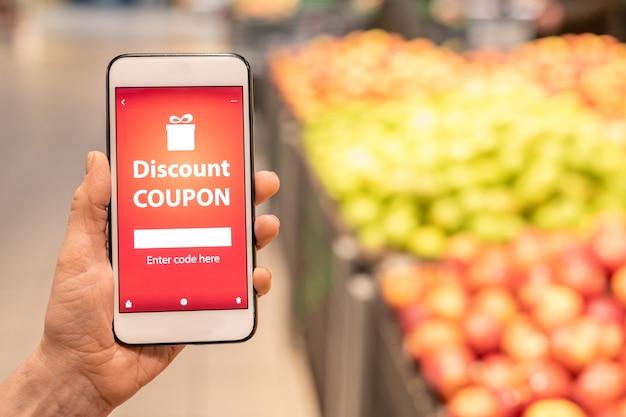 Main de l'acheteur féminin mature contemporain tenant le smartphone et vous montrant un coupon de réduction en ligne lors de la visite d'un supermarché