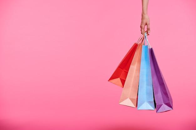 Main de l'acheteur tenant un tas de sacs en papier colorés ou de les transporter après le shopping sur fond rose