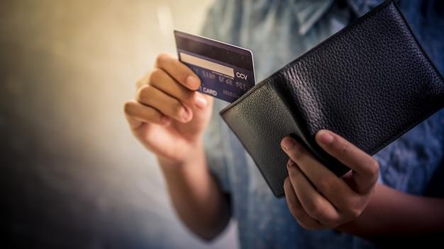 La main de l'adolescent utilise une carte de crédit. elle sort le portefeuille. - images