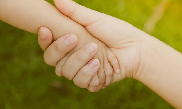 Main adulte saisissant une main de bébé