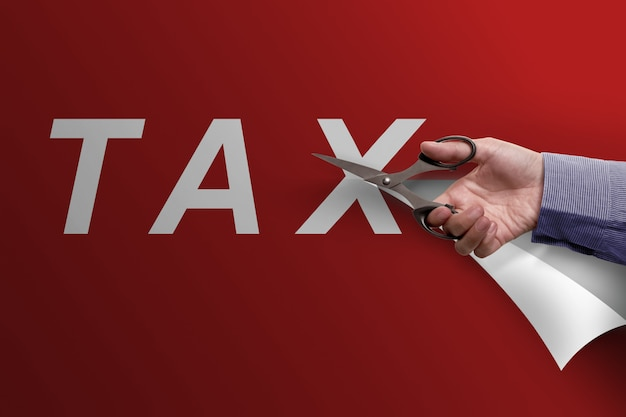 Main d'affaires avec des ciseaux coupe mot impôt