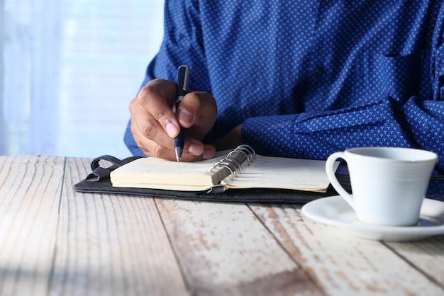 Main d & # 39; affaires écrit avec un stylo sur le bloc-notes sur le bureau
