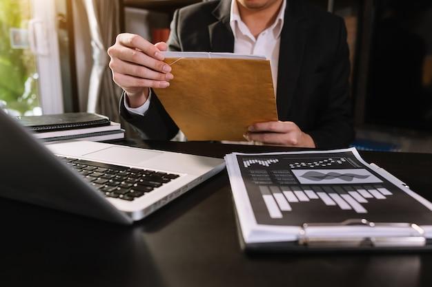 Main d'affaires travaillant avec un nouvel ordinateur moderne et écrivant sur le diagramme de stratégie du bloc-notes comme concept lumière du matin