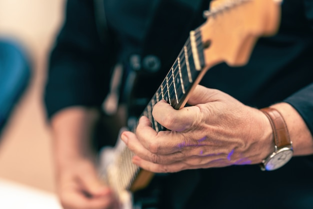 Main âgée d'un musicien jouant de la guitare électrique à l'extérieur