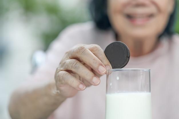 Main âgée trempant un biscuit au chocolat dans un verre de lait