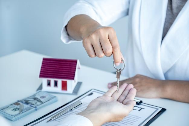 Main de l'agent immobilier, tenez les clés et expliquez le contrat commercial, le loyer, l'achat, l'hypothèque, le prêt ou l'assurance habitation.