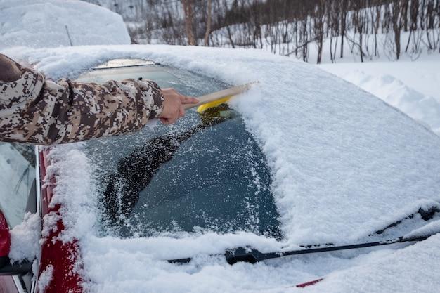 Main à l'aide d'une brosse balayant la neige sur le pare-brise de la voiture en hiver