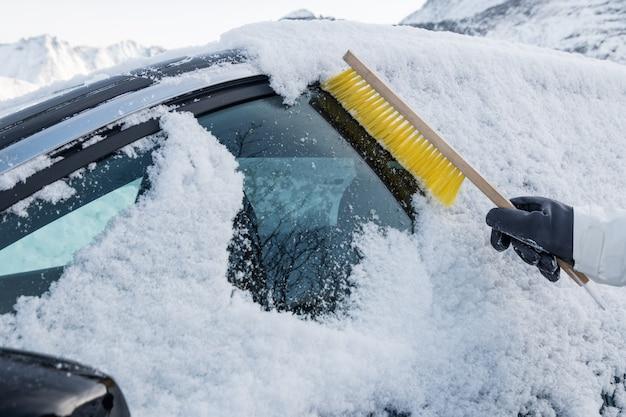 Main à l'aide d'une brosse balayant la neige sur le pare-brise de la voiture