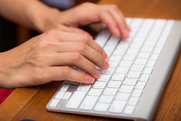 Main à l'aide d'un clavier d'ordinateur sur la table de bureau