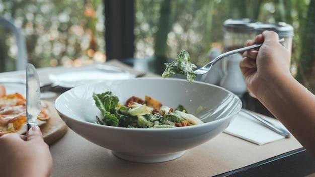 Main à l'aide d'une fourchette pour ramasser une salade ceasar à manger avec une pizza sur une table à manger