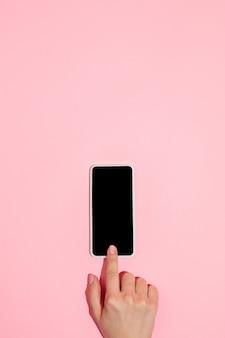 Main à l'aide d'un gadget sur l'écran vierge de la vue de dessus avec un style minimaliste de fond