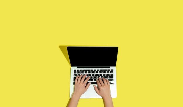 Main à l'aide de gadgets, ordinateur portable en vue de dessus, écran vide