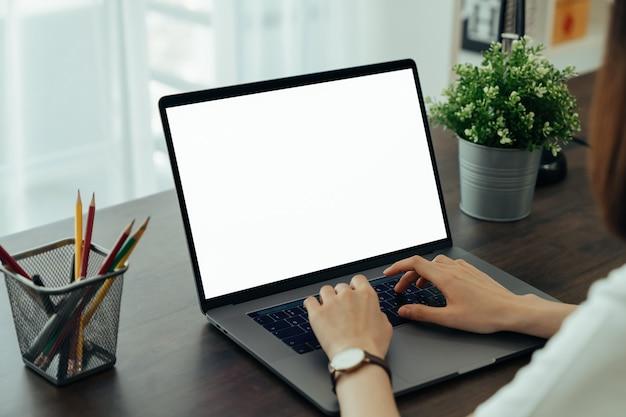 Main à l'aide d'un ordinateur portable avec écran d'espace copie vierge pour votre publicité. sur la table au bureau.