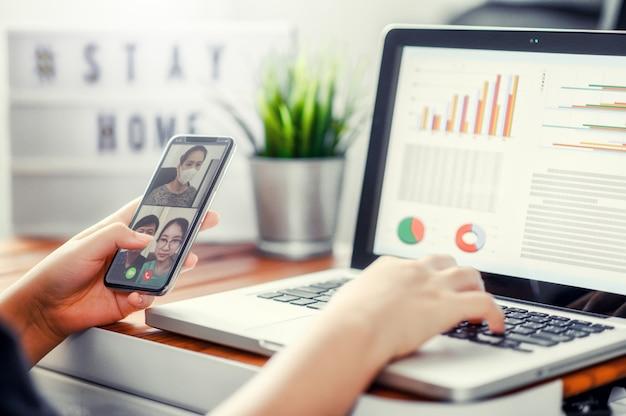 La main à l'aide de smartphone parler virtuel avec des amis, à l'aide d'une conférence de chat vidéo. groupe de personnes intelligentes travaillant à domicile.