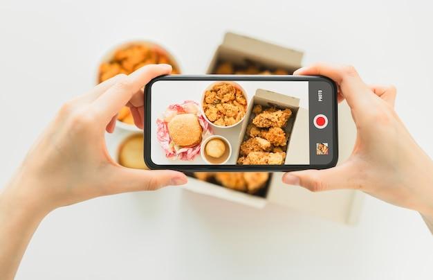 Main à l'aide de smartphone avec photographie de poulet frit de restauration rapide.