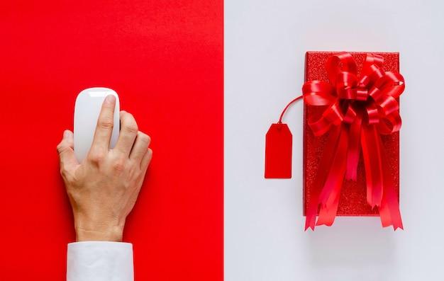 Main à l'aide de la souris shopping en ligne avec boîte de noël rouge et étiquette de prix sur blanc et rouge