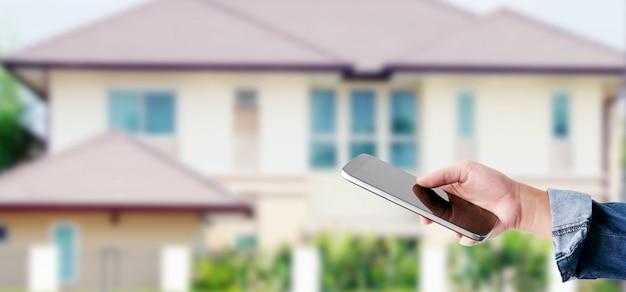 Main à l'aide de téléphone intelligent sur fond de maison flou