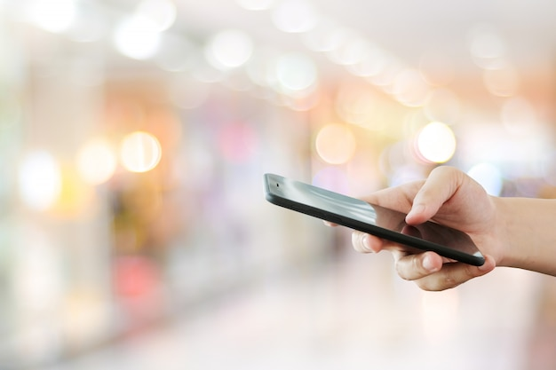 Main à l'aide de téléphone intelligent sur la lumière de bokeh flou, affaires et technologie, internet du concept de choses