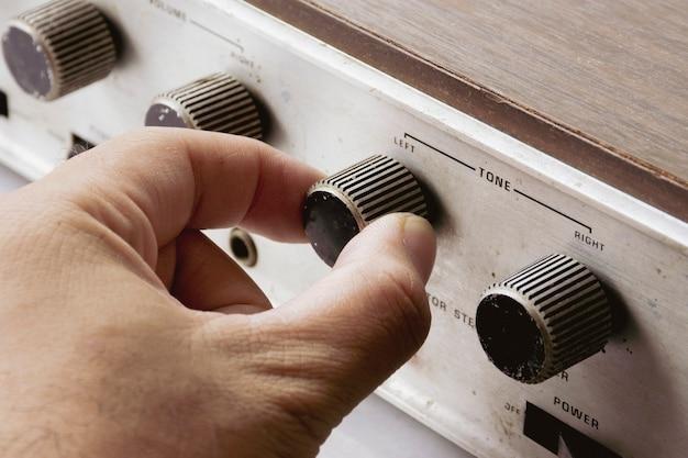 La main ajuste le bouton de volume de tonalité de l'amplificateur intégré vintage