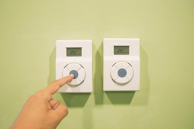 La main ajuste la température au niveau de la télécommande du thermostat.