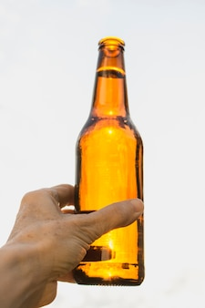 Main angle faible avec bouteille de bière ouverte