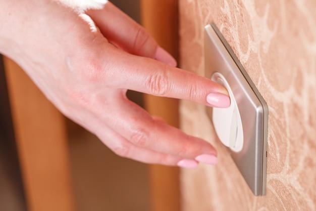 La main appuie sur l'interrupteur d'éclairage sur le mur
