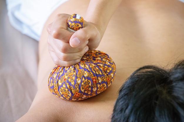 La main appuie sur la presse à base de plantes massage thaïlandais