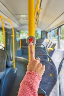 Main appuyant sur le bouton d'arrêt du bus close up