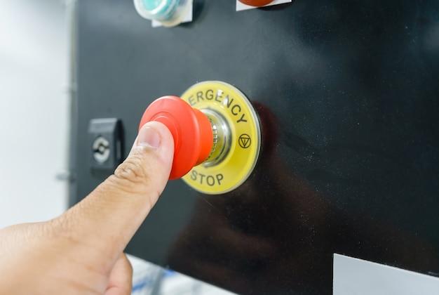 Main appuyant sur le bouton d'urgence rouge ou le bouton d'arrêt pour machine industrielle