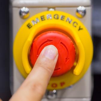 Main appuyant sur le bouton d'urgence rouge ou bouton d'arrêt