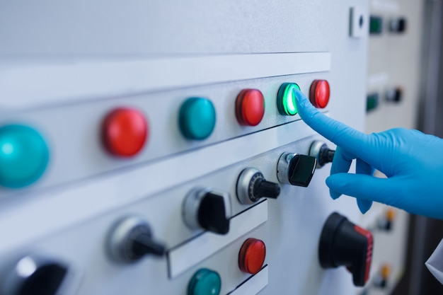 Main appuyant sur le bouton vert de la machine