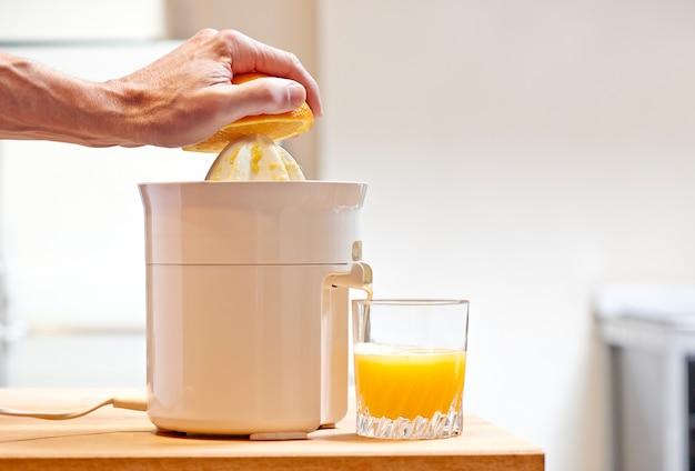 Main en appuyant sur les fruits orange avec presse-agrumes électrique