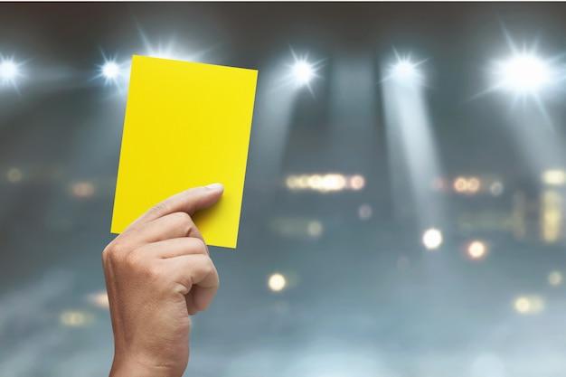 Main de l'arbitre avec un carton jaune
