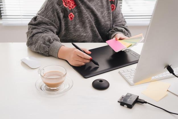 Main d'architecte d'intérieur travaillant avec un nouvel ordinateur portable moderne et une tablette numérique pro