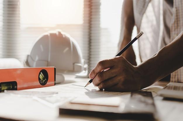 Main architecte professionnel, ingénieur ou mains intérieures dessinant avec blueprint