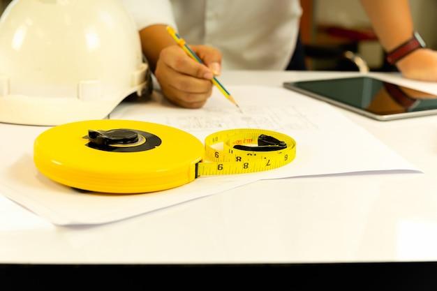 Main d'architecte travaillant sur blueprint avec tablette sur table.