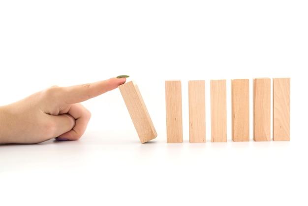 Main arrêtant l'effet de crise d'affaires domino en bois ou concept de protection contre les risques.