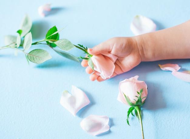Main d'art de mode d'un petit enfant tenant des fleurs sur fond bleu