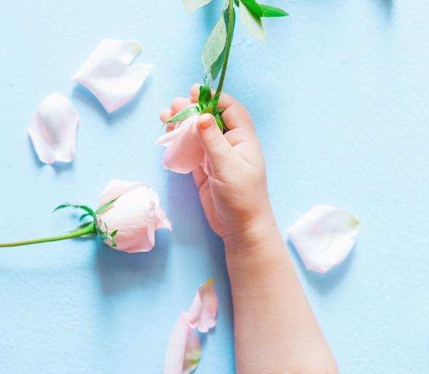 Main d'art de mode d'un petit enfant tenant des fleurs